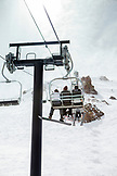 USA, California, Mammoth, groups of individuals pile on and patiently ride the chairlift to the top of the run at Mammoth Ski Resort