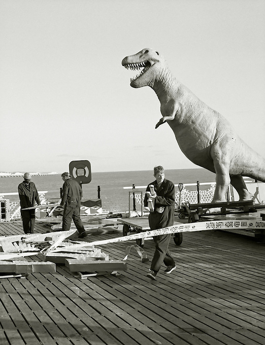 Workmen on the Palace Pier in Brighton seem unperturbed by the dinosaur behind them...