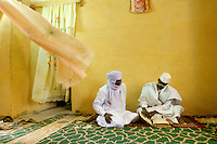 Sidi Alimam (32) works with Abdl Haidara to restore thousands of manuscripts at the newly built Al Moustapha Konate de Maigala library library of Timbuktu. Here he is shown reading an ancient manuscript with his uncle Alphady Ascopfare, (left). In the past few years, with funding from different organizations including the Ford Foundation, thousands of the manscripts are being recovered, stored, preserved and studied. Sadly, many of them have been lost or severley damaged but for those that remain it is a maginifcent reminder of Africa's literary history. /Felix Features