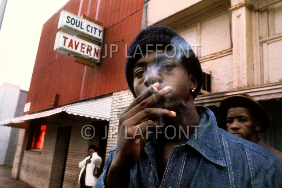 Americus, GA. December 1976. <br /> Unemployed young people gather on the street to wait for job opportunities.<br /> Southerner Jimmy Carter is going to the White House. Born in Georgia, Carter is a democrat with a more open mind. A man who favors racial integration inspite of a majority of white people still living under misserable conditions. Officially, social barriers have been dropped, but racism still exists. If the South is on the rise and if in Georgia average salaries have trippled in the last 15 years, not everyone is benefitting from this economic boom. Perhaps, Jimmy Carter will seriously consider those who are in the lower end of the system's social scales.