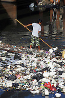 A trash collector moves along a heavily polluted waterway in central Jakarta.<br />