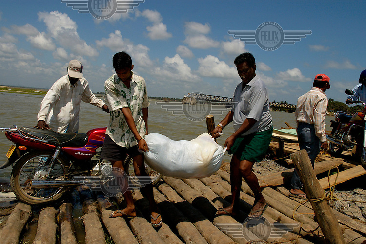 Goods being unloaded from a ferry, being used after the bridge across Arugam Bay (visible in the background) was badly damaged by the tsunami which struck South Asia on 26/12/2004..An underwater earthquake measuring 9 on the Richter scale triggered a series of tidal waves which caused devastation when they struck dry land. 12 countries were affected by the tsunami, with a combined death toll of over 280,000.
