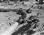 A water main is being placed across the Naugatuck River about 200 yards south of Maple Street under the direction of the Army Engineers. All mains were broken or made unserviceable by the flood a month ago and only one surface main now crosses the river. The new main is expected to be completed in a month. 19 September 1955.