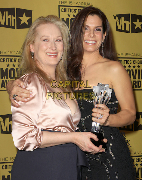MERYL STREEP & SANDRA BULLOCK .15th Annual Critics' Choice Movie Awards Press Room held The Hollywood Palladium, Hollywood, California, USA, 15th January 2010..press room pressroom half length black strapless award winner trophy beaded dress peach pink satin blouse shirt blue dress wrap arm around .CAP/ADM/KB.©Kevan Brooks/Admedia/Capital Pictures