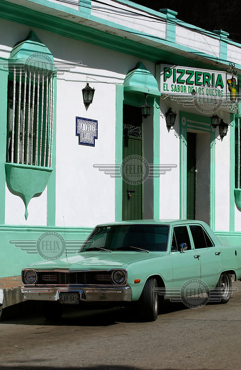 Old car outside a pizza restaurant in the old, colonial part of Merida.