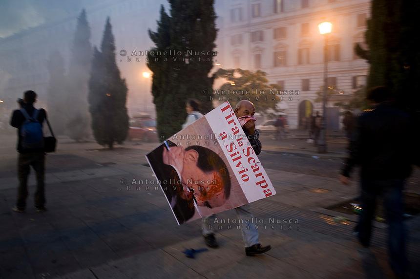 Un manifestante si allontana dal luogo degli scontri portando con se il suo cartello contro Berlusconi.<br /> A demonstrator holds a poster reading 'throw a shoe at Silvio' as a vehicule of Carabinieri is set on fire in the city centre
