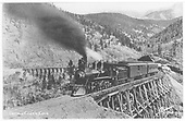 3/4 fireman's-side view of a Colorado Midland 4-6-0 with a 2-car passenger train on a Midland Terminal wooden trestle below Cripple Creek.<br /> Colorado Midland / Midland Terminal  Cripple Creek, CO
