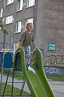 Boy age 3 playing on park slide in front of his Communist built Blok home. Balucki District Lodz Central Poland