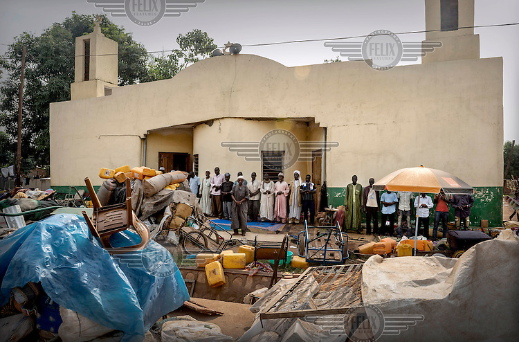 Residents of a Muslim area of the capital gather at a mosque with their belongings. They are surrounded by potentially hostile Christian neighbours and have been under the protection of the French army while they wait to be evacuated. In 2013 a rebellion by a predominantly Muslim rebel group Seleka, led by Michel Djotodia, toppled the government of President Francios Bozize. Djotodia declared that Seleka would be disbanded but as law and order collapsed the Seleka roamed the country committing atrocities against the civilian population. In response a vigillante group, calling themselves Anti-Balaka (Anti-Machete), sought to defend their lives and property but they then began to take reprisals against the Muslim population and the conflict became increasingly sectarian. French and Chadian peacekeeping forces have struggled to contain the situation and the smaller Muslim population began to flee the country.