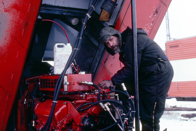 Research and Support vehicles need to be in top shape out on the ice of the Beaufort Sea in this Seismic Research Camp. Camp head Mechanic shown here working on a diesel engine. Circa 1980.