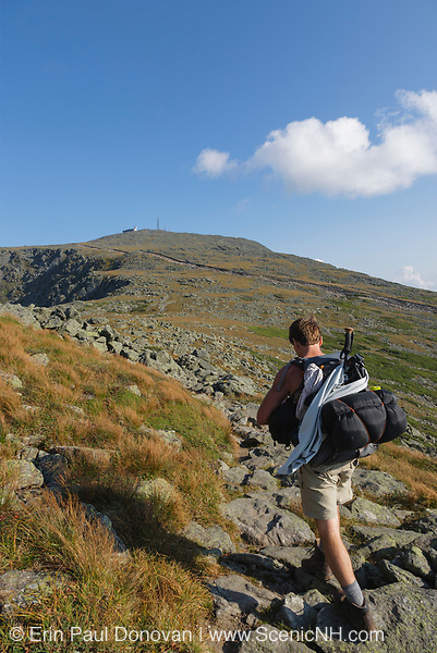 A hiker traveling south on the Appalachian Trail (Gulfside Trail) in the White Mountains, New Hampshire. Mount Washington is in the background.
