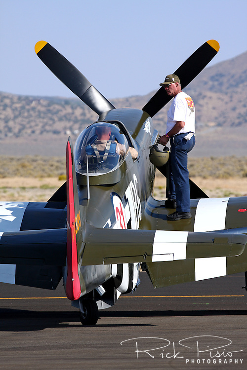"A crewmember stands on the wing of the Unlimited Air Racer ""Speedball Alice"" assisting the pilot to prepare for a heat race during the Reno National Championship Air Races."