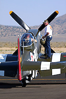 """A crewmember stands on the wing of the Unlimited Air Racer """"Speedball Alice"""" assisting the pilot to prepare for a heat race during the Reno National Championship Air Races."""