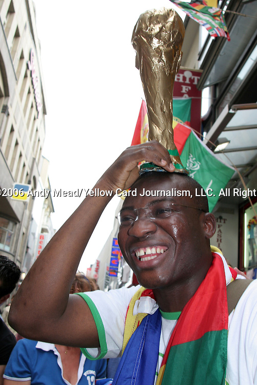 23 June 2006: A Togo fan holds a Jules Rimet trophy on his head. Togo played France at the RheinEnergie Stadion in Cologne, Germany in match 45, a Group G first round game, of the 2006 FIFA World Cup.