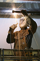 Construction worker welds pipe for the Golden Valley Electric Association