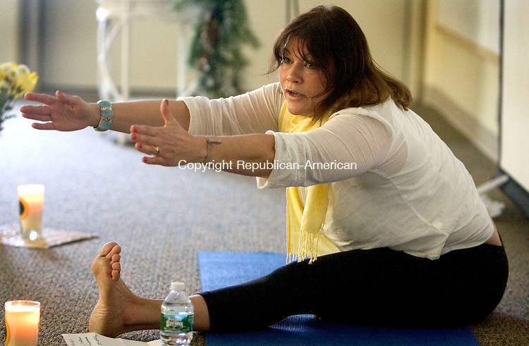 MIDDLEBURY CT. 10 December 2014-011014SV06-Cynthia De Pecol instructs a yoga session during a Holistic Yoga class at the Public Library in Middlebury Friday. The session was designed to promote body-mind harmony. <br /> Steven Valenti Republican-American