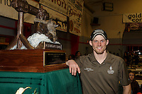 2015 Iditarod champion Dallas Seavey poses next to the Joe Redington Sr. first place trophy at the finishers banquet in Nome on Sunday  March 22, 2015 during Iditarod 2015.  <br /> <br /> (C) Jeff Schultz/SchultzPhoto.com - ALL RIGHTS RESERVED<br />  DUPLICATION  PROHIBITED  WITHOUT  PERMISSION