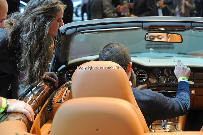 A man sits in the driver seat of the Bentley Continental Flying Spur as a model looks on at the Detroit Auto Show in Detroit, Michigan on January 11, 2009.