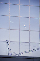 Reflection of Crane and Contrail  in Glass and Steel Office Building London Ontario Canada