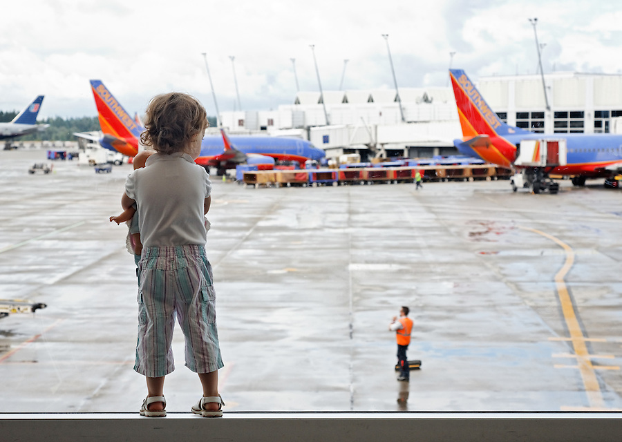 Girl with doll watching airplanes at airport, Sea Tac, Seattle, Washington, USA