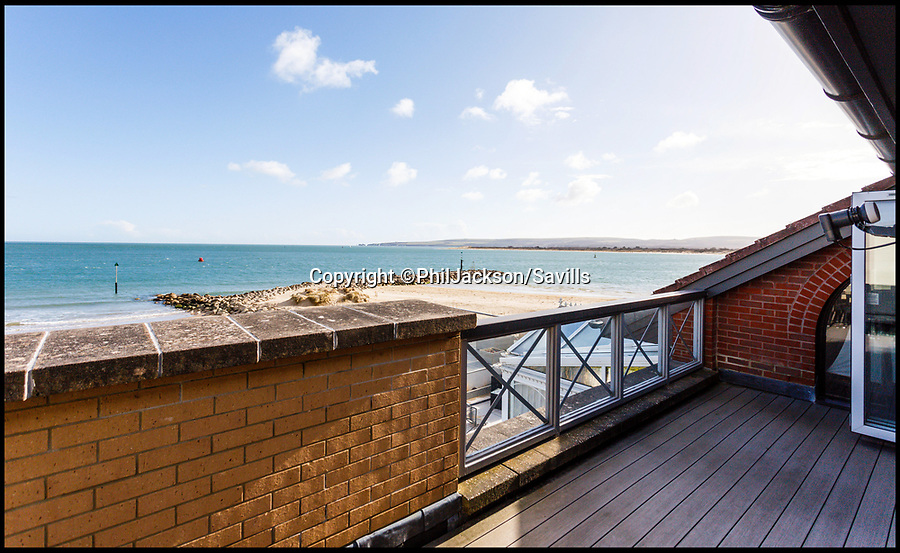 BNPS.co.uk (01202 558833)Pic: Savills/BNPS<br /> <br /> Spectacular views from the apartment.<br /> <br /> The ultimate location, location, location...<br /> <br /> A penthouse flat that sits right on Sandbanks beach and even comes with its own beach hut has gone on the market for £1.675m.<br /> <br /> The four-bedroom apartment enjoys direct access to the sandy beach on the Millionaire's Row in Poole, Dorset. <br /> <br /> And the new owner doesn't fancy the flight of stairs from the seafront to their apartment to get their next bottle of Champagne they can just get one from the fridge in the beach hut that is thrown in with the sale.