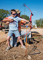 JR Shimon (cq) with his son Cade Shimon (cq, age 7), practice shooting an arrow at a kids area during the U.S. Open Bowfishing Championship, Saturday, May 3, 2014. <br /> <br /> Photo by Matt Nager