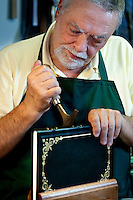 Artisan book-binder (rilegatore) Enrico Gannini, at work in his bottega on Via del Velluti in Florence, Italy