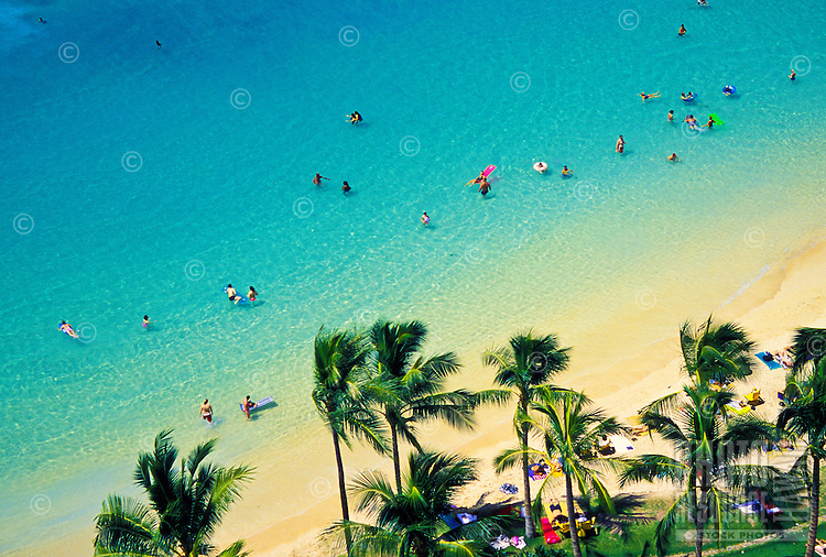 Visitors to Oahu enjoy the warm turquois waters, white sand beaches and swaying palm trees of renowned Waikiki Beach.
