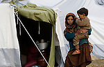 Following an October 8, 2005, earthquake, a girl who survived holds a sibling in a tent city outside Balakot. The quake measured 7.6 on the Richter scale and killed more than 74,000 people in northern Pakistan.