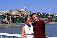 Tourists with self portrait camera on Danube River with Buda Castle in background  Budapest Hungary