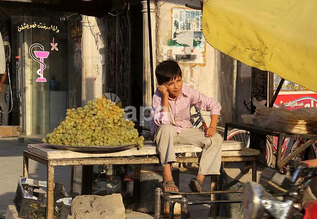 A Syrian boy sells grape in a market in a rebel-controlled area in the northern Syrian city of Aleppo, on August 31, 2015. Photo by Ameer al-Halbi