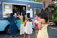 """Hungry attendees to the AfroPunk Festival in Commodore Barry Park in Brooklyn in New York on Sunday, August 26, 2012 enjoy iced drinks from the Kelvin Slush truck at the food truck festival. The festival in the neighborhood of Fort Greene bills itself as the """"other black experience"""" and blends the black punk and hardcore punk scenes. There is also a diverse aspect combining other minority groups, all dressed in their fashionable punk ensembles. (© Richard B. Levine)"""