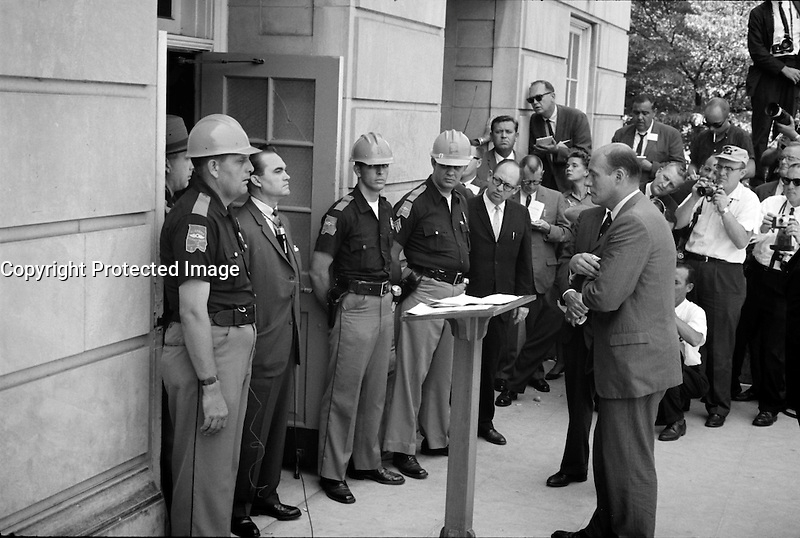 1963  (exact date unknown) Photograph showing Gov. Wallace standing defiantly at a door while being confronted by Deputy U.S. Attorney General Nicholas Katzenbach.