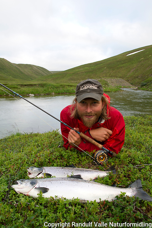 Mann med smålaks fra Sandfjordelva i Varanger. ---- Man and small salmon.