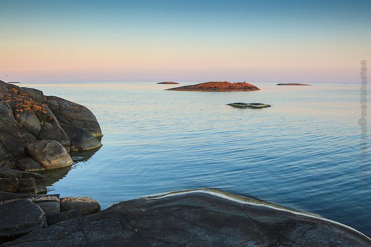 Klippor vid havet i skymning med svag bris och molnfri himmel i Stockholms ytterskärgård.