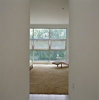 A glimpse into the master bedroom from the corridor towards the pivoting windows which line one wall