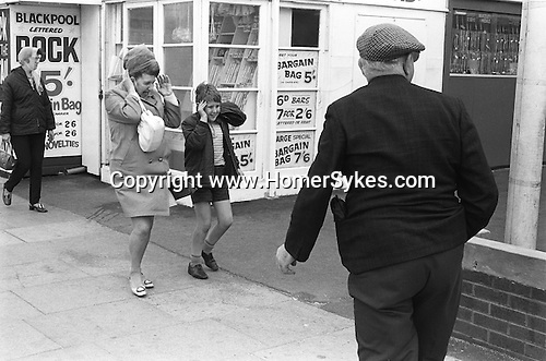 Mother and son blown by strong wind, older man in cloth cap.  Blackpool Golden Mile, Lancashire England 1970.