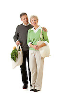 Series with a mature couple, mid 50's, in various themes, including healthy eating, medical and fun.  Isolated on white and an interior room.  Holding groceries in earth friendly shopping bags.