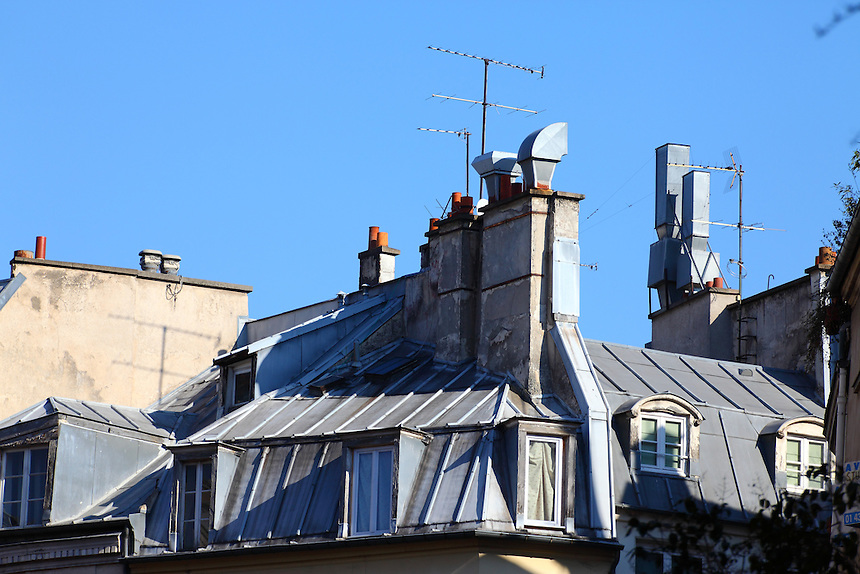Paris Left Bank: A beautiful typical old gray metal mansard roof in the center of Paris, with its windows, its chimney pots and its antennas.<br />