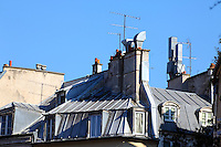 A beautiful typical old gray metal mansard roof in the center of Paris, with its windows, its chimney pots and its antennas. Digitally Improved Photo.