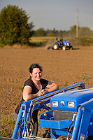 Woman farmer with tractor, liming the soil in a fresh tilled field, Viridian Farms, Oregon