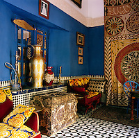 The sitting area has an opulent feel with strong colours and bold, decorative patterns. A tall gold urn stands on a tiled shelf  and red and gold chairs stand on either side.