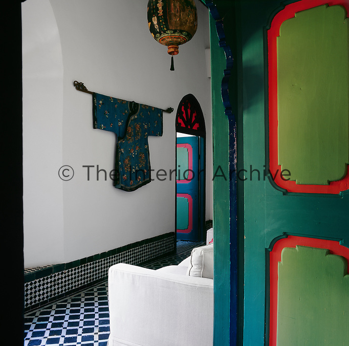 Colourful painted doors lead from the sitting area where the floor is in a blue and white check pattern