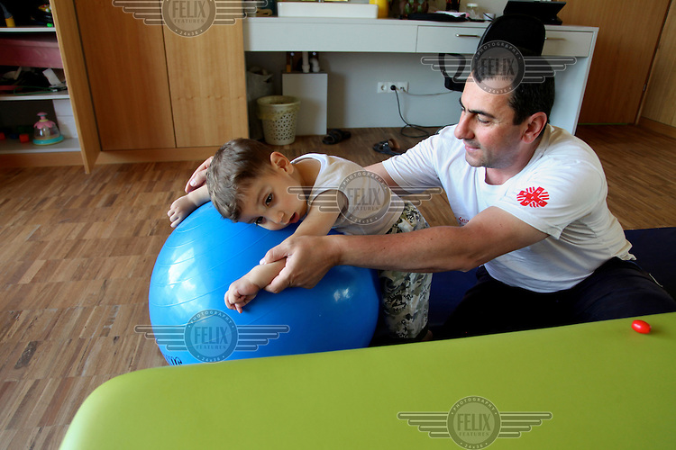 A therapist does exercises with a child at Armenian Caritas, 'Emil's Aregak', a supportive and developmental day care centre for children with disabilities and disadvantaged children.