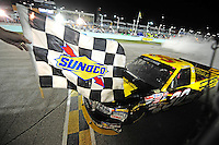 Nov. 14, 2008; Homestead, FL, USA; NASCAR Craftsman Truck Series driver Todd Bodine receives the checkered flag from a NASCAR official after winning the Ford 200 at Homestead Miami Speedway. Mandatory Credit: Mark J. Rebilas-