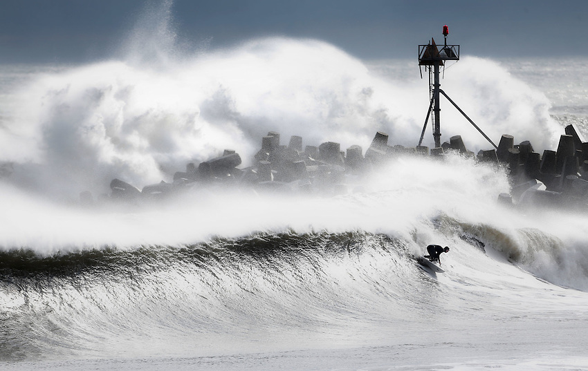 """MANASQUAN, NJ (Dec. 21, 2012) —An unidentified surfer rides a 12-foot wave as an even bigger set explodes over the south jetty of Manasquan Inlet during an epic post-Hurricane Sandy winter surf session now referred to as the """"Doomsday Swell"""""""