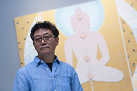 Artist Gonkar Gyatso poses in front of one of his works during the Pop Phraseology exhibition at the Pearl Lam Galleries in Hong Kong on 17 Sept 2014. Photo by Jerome Favre / studioEAST