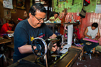 Salvadoran shoemakers work on new shoes, each one focused on a different stage of the production process, in a small shoe making workshop in San Salvador, El Salvador, 16 November 2016.