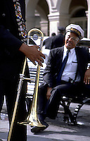 Members of a marching jazz band take a break and and talk; a musican holds his trombone to his side. French Quarter, New Orleans, Louisiana.