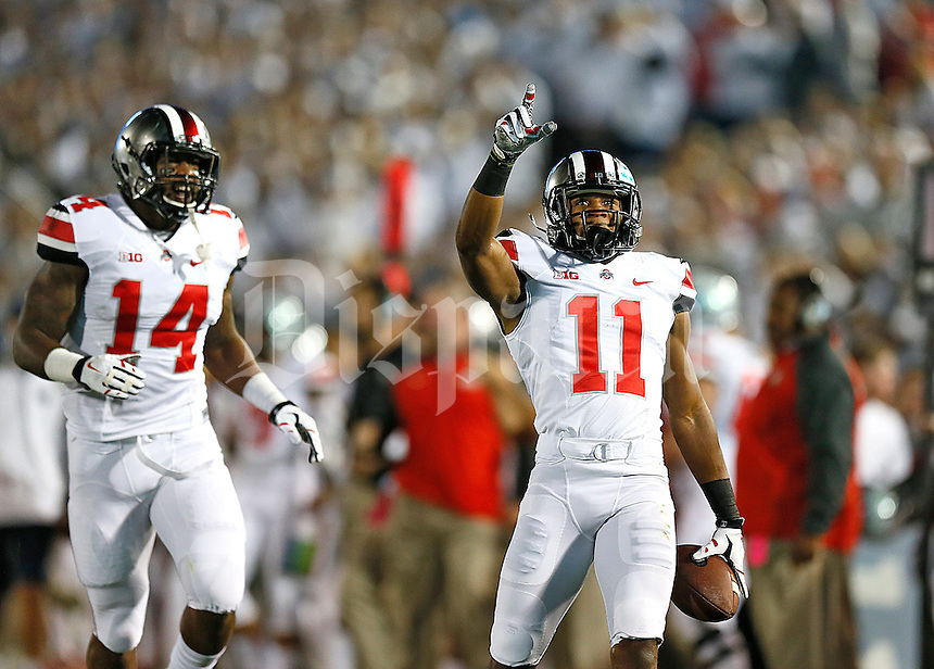 Ohio State Buckeyes defensive back Vonn Bell (11) celebrates his interception with Ohio State Buckeyes linebacker Curtis Grant (14) at Beaver Stadium on October 25, 2014.  (Chris Russell/Dispatch Photo)